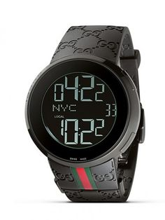 From the I-Gucci collection, a modern timepiece. Black bezel casing frames a round black dial that offers the option of a digital or analog display. White digits represent hour, minute, second, date and your location. Black rubber strap with red/green webbing accent. Triple deployment buckle.