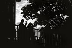 Black and white photo of a man at a wedding smoking a cigarette