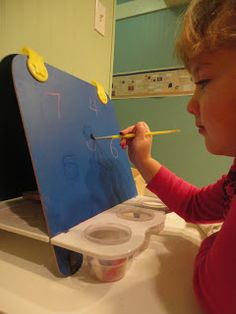 Discovery Days and Montessori Moments - brushing water over chalk board letters and numbers to practice writting