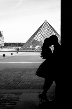 Silhouette picture at Louvre Museum with a view over the Pyramid, taken during a Paris engagement photo session.