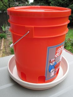 "Chicken feeders are insanely expensive...or maybe I'm just insanely cheap. $30+ for a bucket with holes in it just seemed wrong to me. I made this one from a Home Depot bucket bolted to a 16"" plant saucer, for a total cost of about $8. If you look closely you can see openings around the bottom of the bucket (made using my trusty Dremel tool) for the feed to come out of. I left the handle on the bucket so I can hang the feeder if I want to."