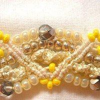 Náramek z bílé bavlněné příze a korálků ve stříbrné a žluté barvě, je 2 cm široký a 20 cm dlouhý vč. zaklapávacího zapínání. Technikou makramé je vytvořen vzor cik-cak a navlečené korálky zase oblouky. Náramek je velmi efektní a dá se nosit k běžnému i slavnostnímu oblečení.