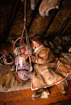 Inside a reindeer skin tent a Nenets mother comforts her baby. Yamal, Siberia, Russia