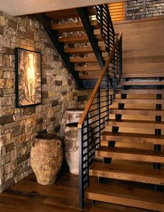 Great metal stairway with open wood risers. Wood and stone walls for the enclosure.