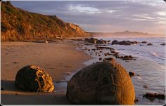 Strange Places - THE MOERAKI BOULDERS OF NEW ZEALAND It is said by the Maoris that some of the surviving crew of the Araiteuru canoe were turned into stone and became mountains. The Moeraki boulders are said to be the pots and chattels from the canoe. Strange Places, Mysterious Places, Places Around The World, Around The Worlds, Moeraki Boulders, Islands In The Pacific, New Zealand South Island, Rock Formations, Places Of Interest