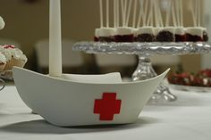 """white candles with cute craft foam nursing hats. They also printed some pictures from the internet ( googled """"vintage nurse illustrations"""") and put them in white frames. They looked really cute laying on the tables."""