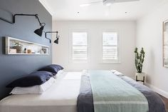 "Chloe painted most of the apartment a crisp white to maximise the natural light coming in, but the dark feature wall in the main bedroom removes the need for a headboard. The inset stone shelf above the bed is from [Gitani Stone](http://www.gitanistone.com.au/?utm_campaign=supplier/|target=""_blank"")."