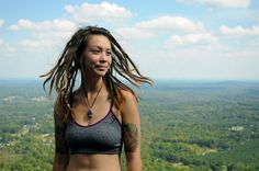 Beautiful woman with shoulder length dreads in jog top smiling with clouds in background.   I love her dreads ... definitely looks in her element.  @David Nilsson Nilsson Adams