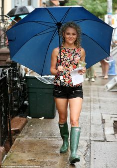 Smiling in the rain: AnnaSophia Robb carried a big umbrella as she strolled to the New York set The Carrie Diaries in tiny shorts and green ...