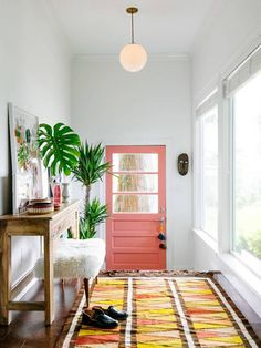 pink door, mid-century globe light, plants, console, sheep skin stool, yellow rug