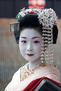 This woman is likely an authentic Maiko (or Hangyoku if from Tokyo).  Maiko & Geisha (or Geiko if from Kyoto) wear similar makeup.  The main difference in makeup is the lipstick, the Maiko will only paint the bottom lip red, or if a Maiko is senior, thin line on both lips.  A Geisha will paint both their lips fully red.  Also, Maiko use a noticeable amount of red makeup around the eyes & eyebrow. They also use more pink on their cheeks & around their eyes.