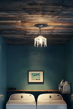 A wood plank ceiling with the popping wall colors...perfect! amazing color scheme! love the chandelier in the laundry alcove!