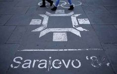 People Walk Past The Logo Of The Winter Olympics In Central Sarajevo | 24 Spooky Photos Of Sarajevo's Abandoned Olympic Venues