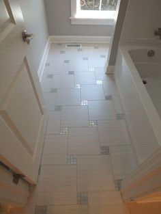 Bathroom floor with mosaic inlays. Beautiful tile layout and contrast between semi-matte and shiny.