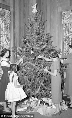 The start of a Christmas tradition: In the 1900s (L), trees were often adorned with large mismatched ornaments as well as pierced tin, to create  lanterns to hold candles which shone through the holes, serving to add the same twinkly glow that is now supplied by electric lights. From 1910 (C), Christmas trees became even bigger, as people grew more enamored with the idea of having their own fir tree at home. This continued on into the 1920s (R), which is when the concept of a tree topper…