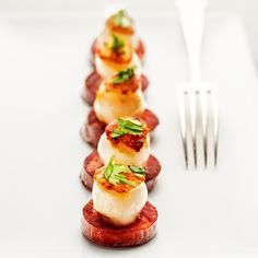 A simple, luscious little appetiser with tons of flavor: spicy chorizo topped with seared sea scallops.