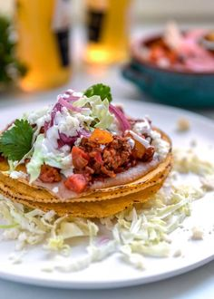 Not low carb -- Diced potatoes and carrots are added in this saucy ground beef, tomato and cumin filling all layered on top of refried beans for these Ground Beef Tostadas. #tostada #beef