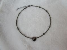 Necklace with pyrite and quartz beads, and unknown heart shaped bead.