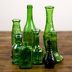 """assorted green glass: Assorted green glass bottles and vases varying in size from 2"""" to 12"""""""