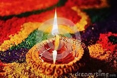 Glowing diya with rangoli in the background decorated on occasion of diwali festival