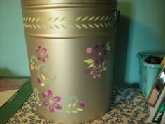 Painted over an old popcorn tin, using Krylon spray paint, then added stencils