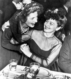 Both up for the best actress trophy, Joan Fontaine and Olivia De Havilland wish each other luck at the Academy Awards banquet. Fontaine ultimately won. February, 1942