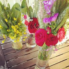garden table with glass bottles of fresh flowers