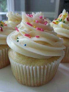 Vanilla gluten free cupcakes with vanilla frosting and colored sprinkles