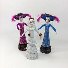 These papel mache catrinas were handmade in Jalisco, Mexico and though they are a little sleepy looking with their dark circles around the eyes, they are a traditional, rustic paper mache folk art. The bride is decorated with white lace and gold glitter and holds her bouquet of roses. The