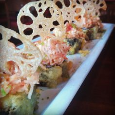 Viva Las Vegas Roll (RA Sushi) Kani kama crab & cream cheese rolled in rice & seaweed, lightly tempura battered & topped with spicy tuna, kani kama crab mix & sliced lotus root; finished with a sweet eel sauce & spinach tempura bits.