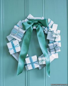 Cover small containers, such as old jewelry boxes, with weatherproof paper, which will hold up outdoors, unlike wrapping paper; seal with all-weather tape. Add decorative bands in contrasting colors, if desired, and tie with ribbon. Attach to a flat wooden wreath form (ours is 18 inches) using a hot-glue gun. Affix a satin bow.