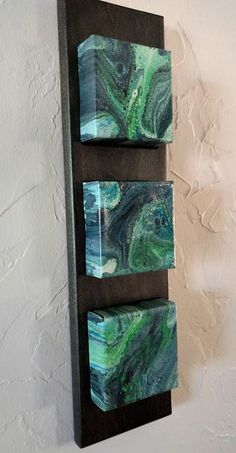 BRAND NEW ITEM! Acrylic pour painting on 4 x 4 x 1 canvas blocks, inset 1/4 in stained solid wood frame making the overall dimensions 5 1/2 x 19 1/2. Sawtooth hanger on back. One of a kind painting. Canvas sealed with gloss varnish. Frame is custom made out of solid Poplar, stained