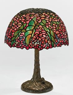 """Tiffany Studios -  """"PONY BEGONIA"""" TABLE LAMP -    with a small """"Tree"""" base shade with small early tag impressed TIFFANY STUDIOS/NEW YORK base impressed TIFFANY STUDIOS/NEW YORK/384 leaded glass and patinated bronze, 16 7/8  in. (42.9 cm) high 13 1/4  in. (33.7 cm) diameter of the shade circa 1905"""