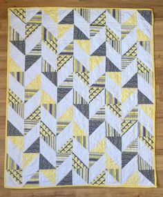 Herringbone Half Square Triangle Baby Quilt | Yellow, gray, and white baby quilt. Half square triangles patchwork pieces are arranged to make a herringbone pattern.