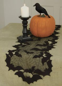 Table runner -- black netting + paper/foam bats to edge it? Or sheer fabric, using paint pen to make spiderwebbing.
