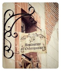 I would like my sign to hang out like this, rather than being flat against the building, so it is more easily seen.  I also think the curvy iron hook holding up the sign is very elegant and pretty.