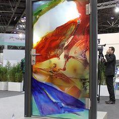 GLASKONSTRUKTION - Im Glasbaubereich projektieren wir    Eingangsbereiche, Windfänge, Ganzglasanlagen, Glasskulpturen und Brandschutzgläser. Alle diese Objekte können auch eine Veredlung in unterschiedlichen Formen und Techniken erfahren. Gestaltete rahmenlose Ganzglastür als Brandschutztür.