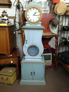 Sold - This is a battery operated clock with two cabinet doors in the base and they single door in the center. Paint with a soft blue accented in gold and distressed. The cabinet measures 19 inches across the front at the widest point. It is 12 inches deep and stands approximately 60 inches tall. It can be seen in Booth E8 at Main Street Antique Mall 7260 East Main St ( E of Power Rd ) Mesa 85207  (contact info hidden) open 7 days 10 till 530 Cash or charge accepted