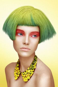green hair bob with lemon lime yellow roots, bangs, crazy makeup, and fruit necklace