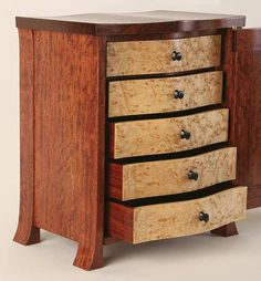 Bubinga cabinet with birdseye maple drawer fronts . carved ebony drawer handles