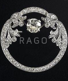 "ART DECO DIAMOND PLATINUM ORNAMENTAL CIRCLE BROOCH Principal OEC diamond, 1.40 cts. by formula, and diamond melee, approx. 1.50 cts. TW, millegrain details. 8.4 gs., 1 1/2"""