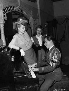 Medium BTS shot of Lucille Ball as herself, Virginia Weidler as Helen Schlesinger and Tommy Dix as Bud/Elwood C. Hooper wearing military academy uniform while playing piano.
