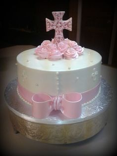 """A 10"""" butter cream cake. Cross topper is white chocolate..butter cream roses, fondant ribbon wrap & bow."""