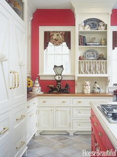 This otherwise neutral kitchen designed by Beverly Ellsley gets a dose of energy from a vibrant red.   - HouseBeautiful.com