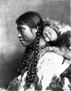 """Format of original: glass negative : b&w ; 5"""" x 7"""" Photographer/Illustrator: Lomen Brothers, Nome, Alaska Remarks: Studio portrait. Hair braided, and baby asleep on her back. Subject(s): Inuit - Children / Inuit - Clothing / Inuit - Personalities / Inuit"""