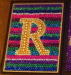Not a fan of this artwork specifically, but like the idea of using beads of one color for the foreground and others for the background stripes. [Mardi Gras bead art Initials and Fleur de Lis by TheBeadifulLife]