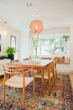 Beautiful earthy dining room design with patterned rug, warm wood dining set and…