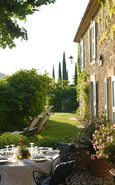 La Bastide de Marie. Shutters. Stone. Tall columnar trees. Lanterns. Terrace. Lawn. Traditional eaves detail.