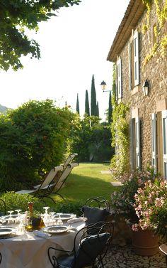 La Bastide de Marie. Shutters. Stone. Tall columnar trees. Lanterns. Terrace. Lawn. Traditional eaves detail.