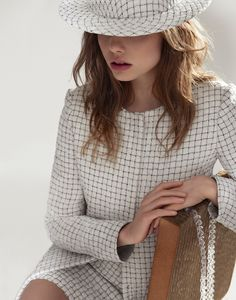 Kristine Froseth models a printed boater hat with a black and white tweed jacket and skirt from Chanel